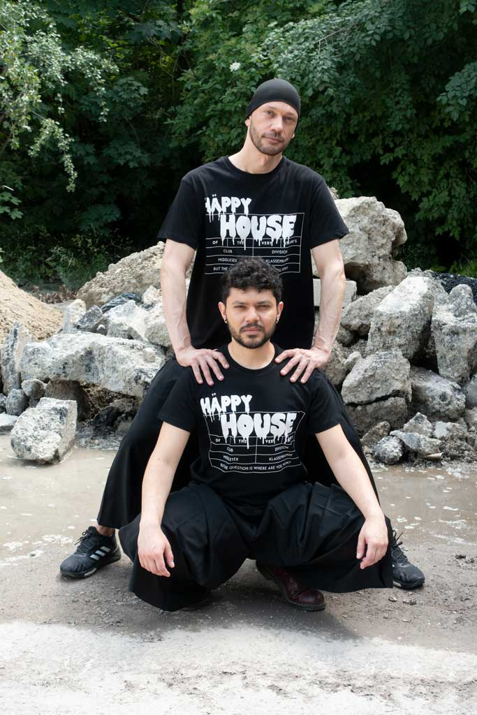 Two men in front of rocks and wood wearing Happy House, a black 4XL T-Shirt by House of the House.