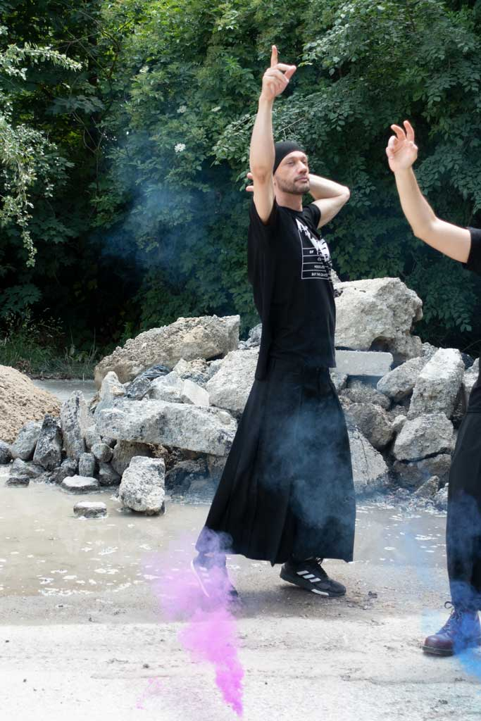 A man dancing amidst smoke wearing a black skirt and Happy House, a black 4XL T-Shirt by House of the House.