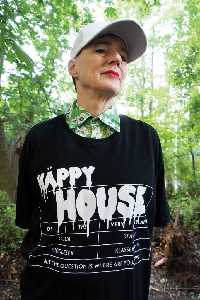 Artist Ashley Hans Scheirl standing in a forest wearing Happy House, a black 4XL T-Shirt by House of the House.
