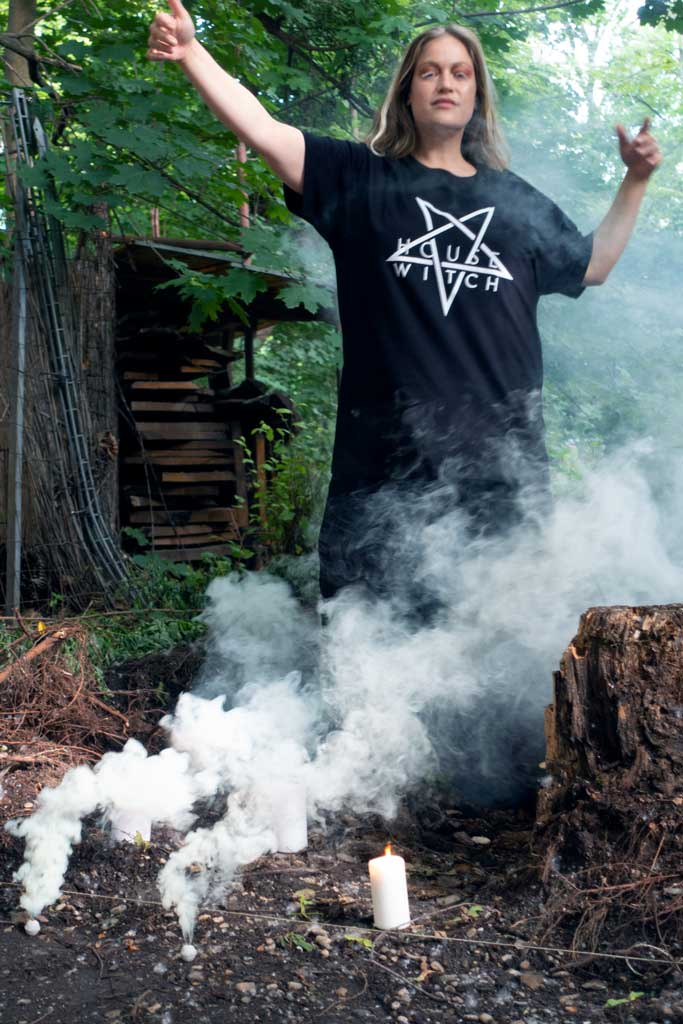 Artist Denise Kottlett dancing mysteriously through smoke in the woods wearing Witch House, a black 4XL T-Shirt by House of the House.