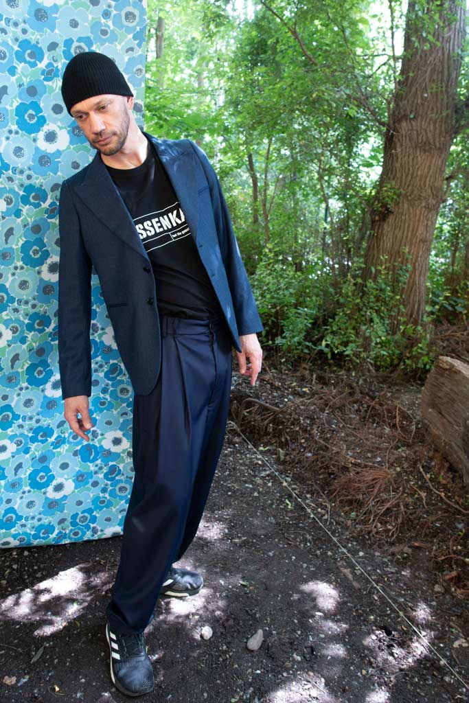 Man in front of a piece of blue flower tapestry wearing a fashionable suit and Klassenkampf, a black 4XL T-Shirt by House of the House.