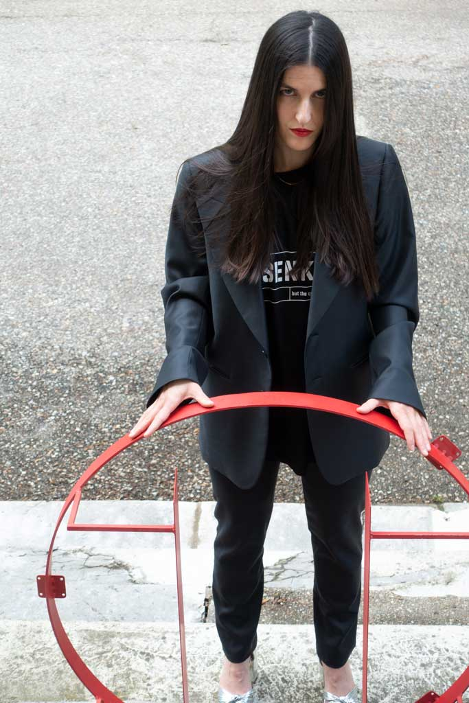 Woman wearing a fashionable suit and Klassenkampf, a black 4XL T-Shirt by House of the House.