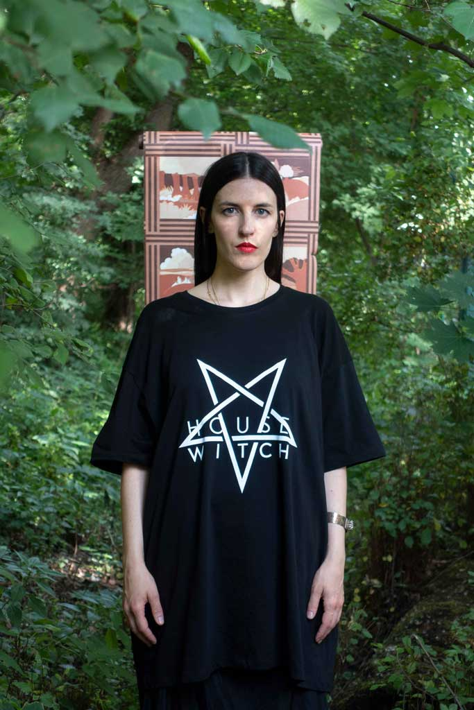 Woman standing in front of a role of tapestry amidst woody vegetation wearing Witch House, a black 4XL T-Shirt by House of the House.